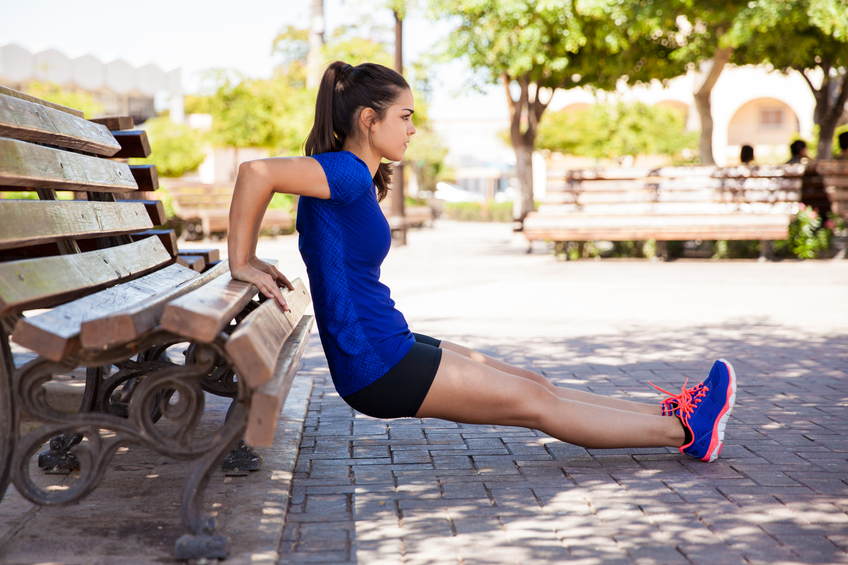 Profile view of a female athlete doing some tricep dips on a park bench